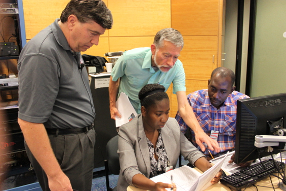 Meteorologists from the Caribbean region complete a practical exercise with assistance from Senior Hurricane Specialist Jack Beven during the 2013 World Meteorological Organization (WMO) Regional Association IV (RA-IV) Workshop on Hurricane Forecasting and Warning.